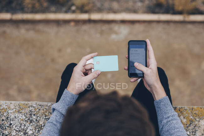 Close-up of a boy paying with the credit card on his mobile phone from above — Stock Photo