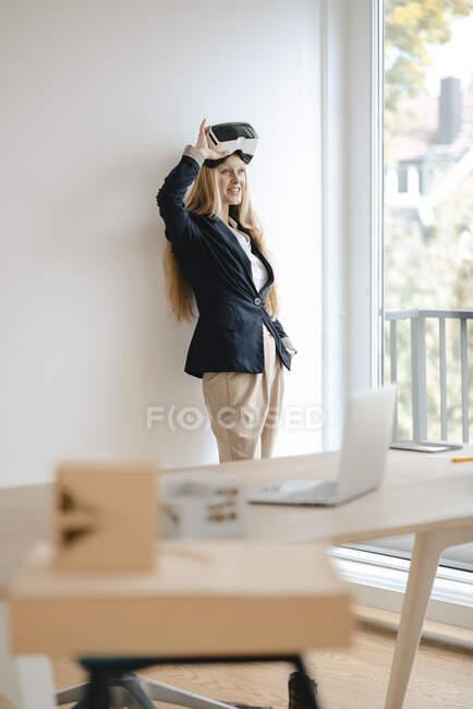 Joven empresaria sonriente con gafas VR en la oficina - foto de stock