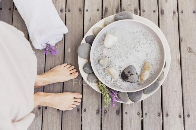 Крупный план женских ног рядом с чашей с водой — стоковое фото