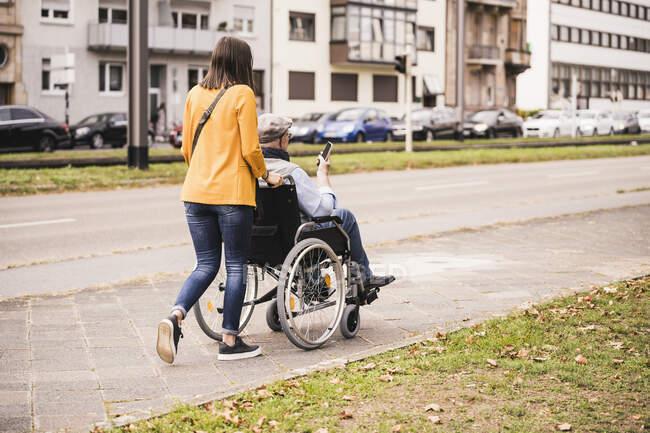 На задньому плані молода жінка штовхає старшого чоловіка зі смартфоном у інвалідному візку на тротуарі. — стокове фото