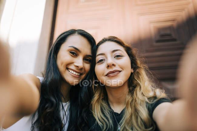 Retrato de dos amigos felices tomando selfie - foto de stock