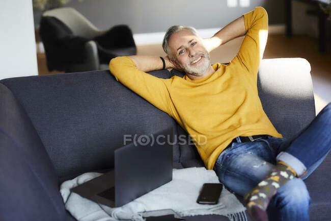 Портрет усміхненого зрілого чоловіка, який відпочиває вдома. — стокове фото