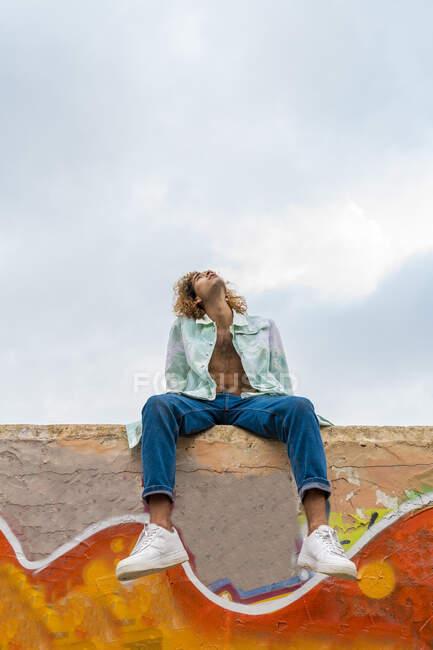 Молодий блондинець сидить на стіні і дивиться вгору. — стокове фото