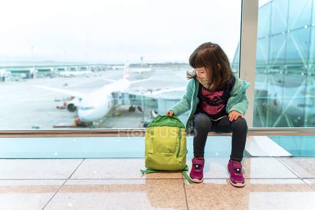 Chica con mochila sentada en el aeropuerto delante de un avión - foto de stock