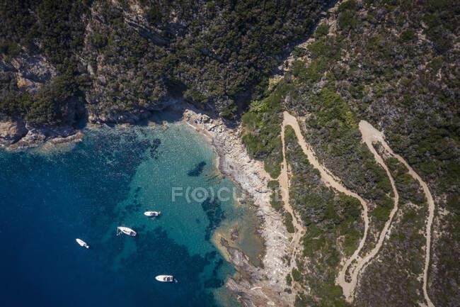 Italia, Provincia di Livorno, Elba, Veduta aerea di strade tortuose e barche galleggianti in acque blu costiere — Foto stock