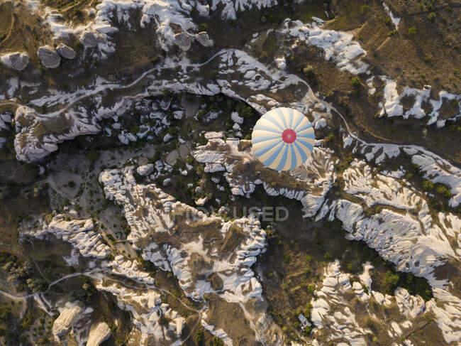 Vue aérienne d'une montgolfière survolant des formations rocheuses au parc national de Goreme, en Cappadoce, en Turquie — Photo de stock