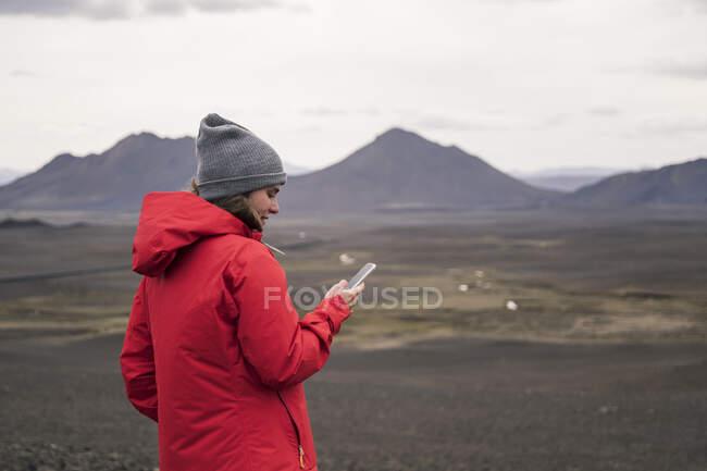 Молода жінка користується смартфоном в ісландському нагір