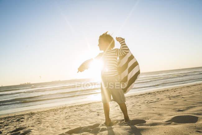 Ragazzo con un asciugamano in piedi sulla spiaggia al tramonto — Foto stock
