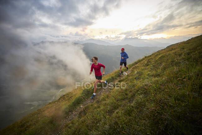 Мужчина и женщина бегут в горах — стоковое фото
