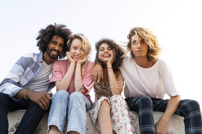 Portrait of happy friends sitting on a wall outdoors — Stock Photo