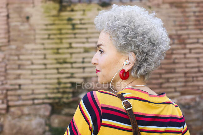 Profile of pierced mature woman with ear phones — Stock Photo