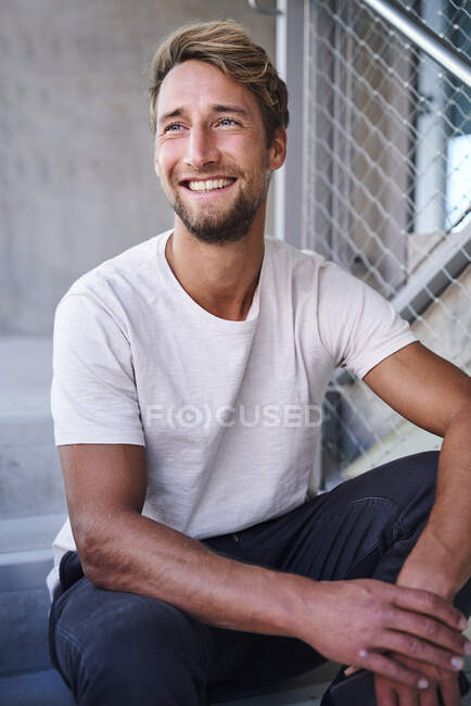 Portrait of smiling young man wearing white t-shirt sitting on stairs — Stock Photo