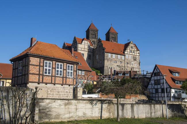 Alemania, Sajonia-Anhalt, Quedlinburg, Vista de bajo ángulo de la Abadía de Quedlinburg y casas de entramado de madera circundantes - foto de stock