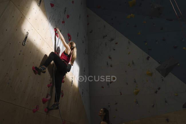 Mulher escalando na parede no ginásio de escalada com luz solar e sombra — Fotografia de Stock