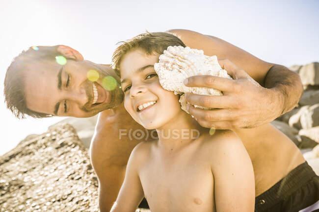 Padre e figlio si divertono sulla spiaggia e ascoltano l'oceano in una conchiglia — Foto stock