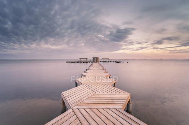 Spain, Murcia, Santiago de la Ribera, Wooden pier on calm sea at sunset — Stock Photo