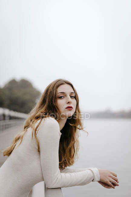 Portrait of young woman wearing white dress, leaning on railing on rainy day — Stock Photo