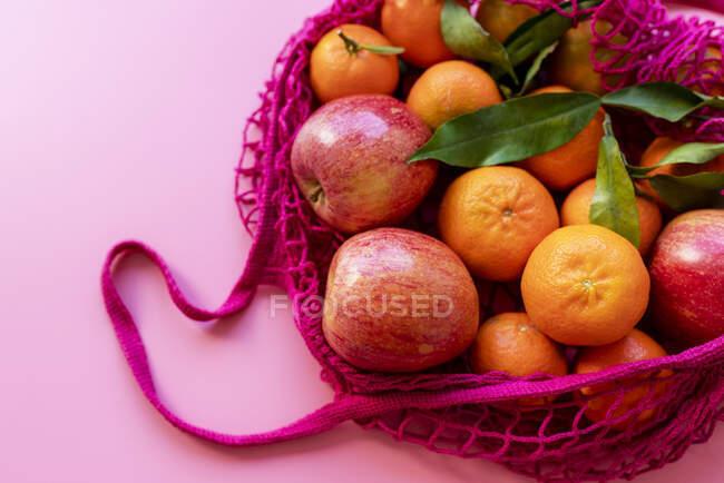 Clémentines et pommes fraîches dans un sac en maille réutilisable écologique — Photo de stock