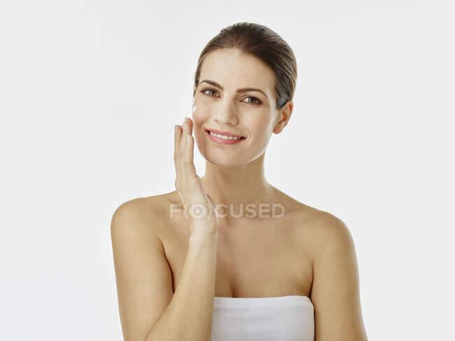 Retrato de mujer sonriente aplicando crema hidratante en su cara - foto de stock