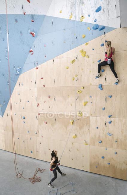 Жінка з напарником на стіні в спортзалі. — стокове фото