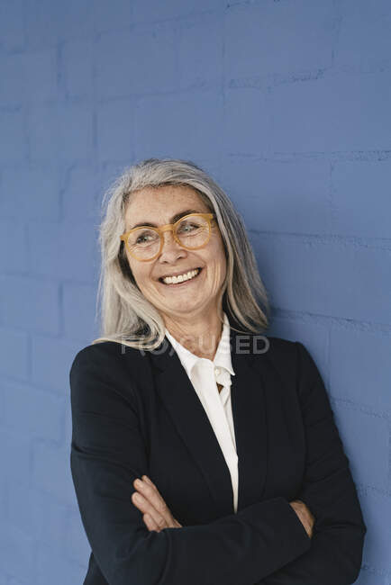 Portrait of smiling grey-haired businesswoman standing at a blue wall — Stock Photo