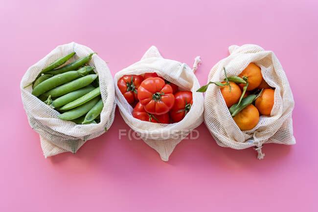 Sacs en mesh réutilisables respectueux de l'environnement avec pois verts frais, tomates et clémentines — Photo de stock