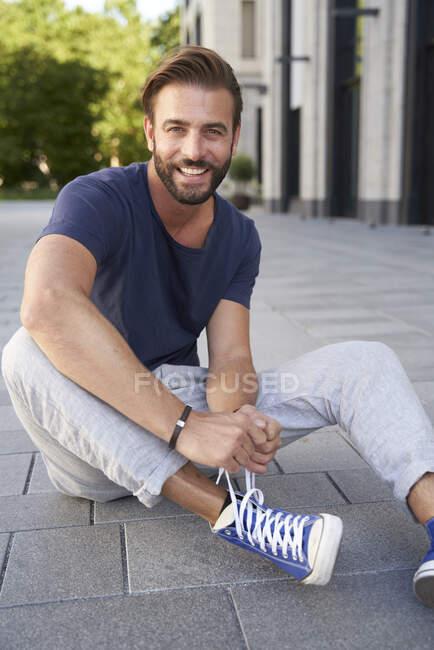 Ritratto di uomo sorridente seduto a terra in città che si allacciava le scarpe — Foto stock