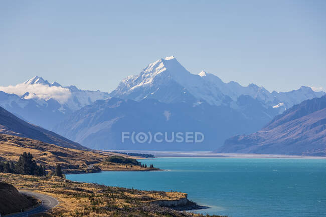 New Zealand, Clear sky over turquoise shore of Lake Pukaki with Mount Cook looming in background — Stock Photo