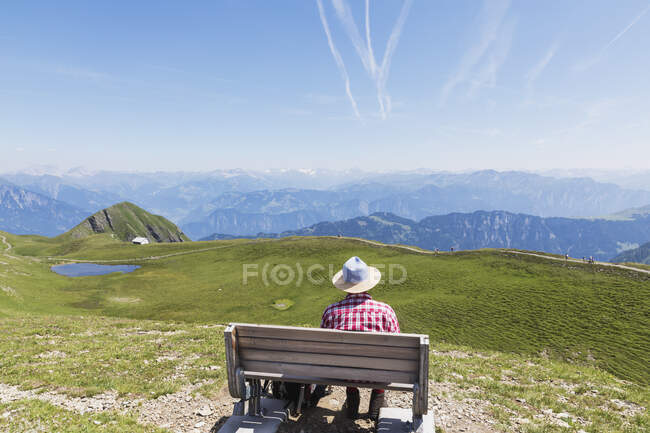 Switzerland, St Gallen Canton, Man resting on bench, looking on the mountains — Stock Photo