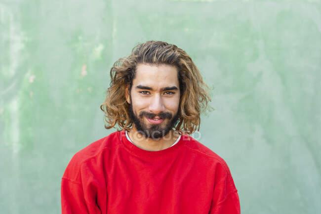 Porträt eines bärtigen jungen Mannes mit rotem Sweatshirt vor grüner Wand — Stockfoto