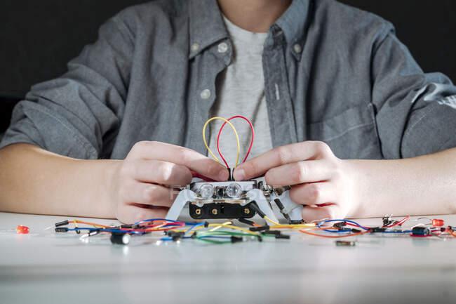 Junge baut Roboter zu Hause zusammen — Stockfoto