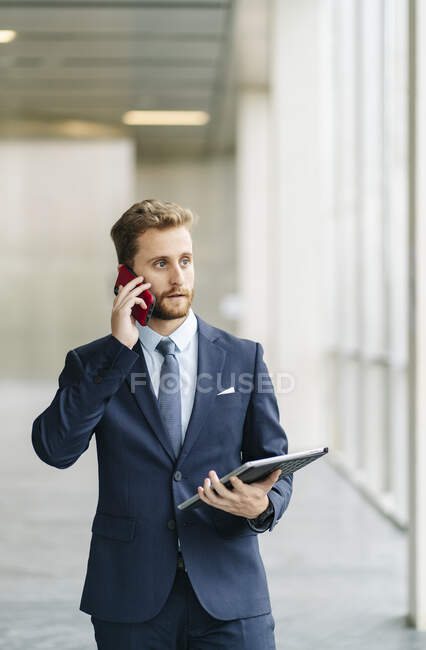 Businessman holding tablet talking on the phone — Stock Photo