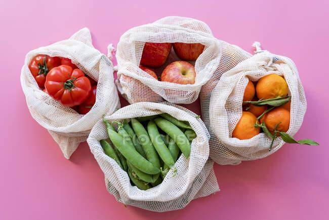 Bolsas de malla reutilizables ecológicas con guisantes verdes frescos, tomates, manzanas y clementinas - foto de stock