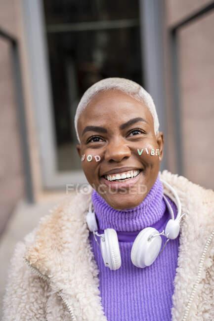 Retrato de mujer madura de pelo blanco con auriculares blancos y pegatinas en la cara, buenas vibraciones - foto de stock