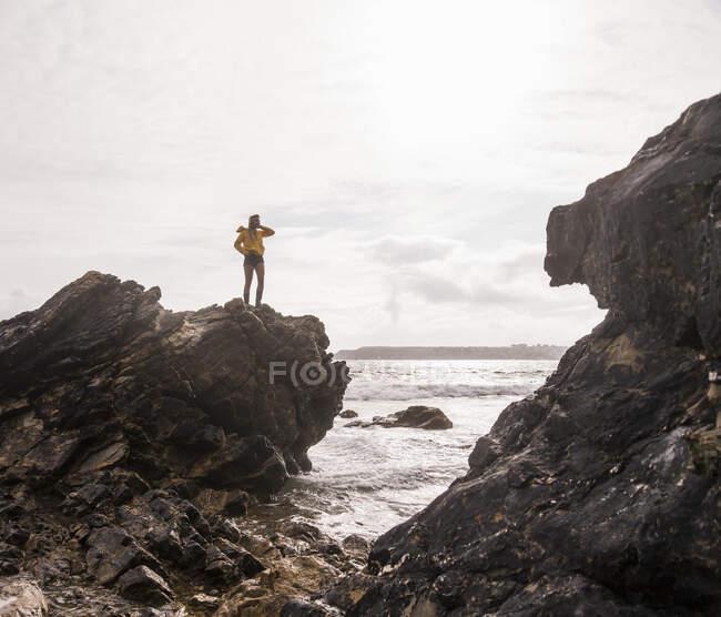 Woman wearing yellow rain jacket standing on rock — Stock Photo