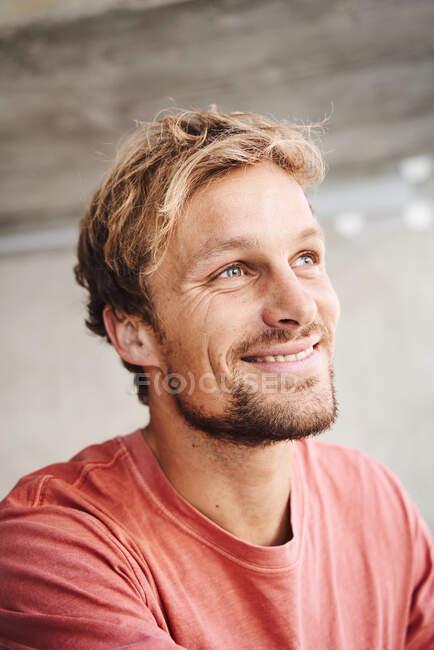 Retrato de un joven sonriente con camiseta mirando hacia arriba - foto de stock