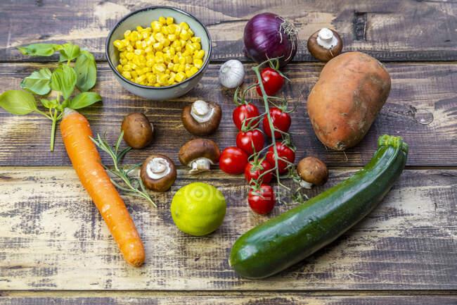 Ingredients for sweet potato curry (sweet potato, zucchini, mushrooms, corn, tomatoes, onions, garlic, lime, basil) — Stock Photo