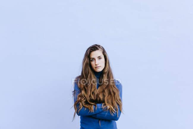 Retrato de mujer joven con jersey de cuello alto azul frente a la pared azul claro - foto de stock