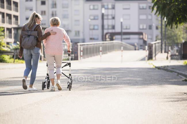 Дідусь допомагає бабусі ходити з колісним ходунками. — стокове фото