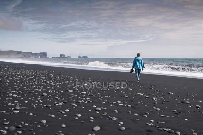 Молода жінка, ходячи босоніж на лавовому пляжі в Ісландії. — стокове фото