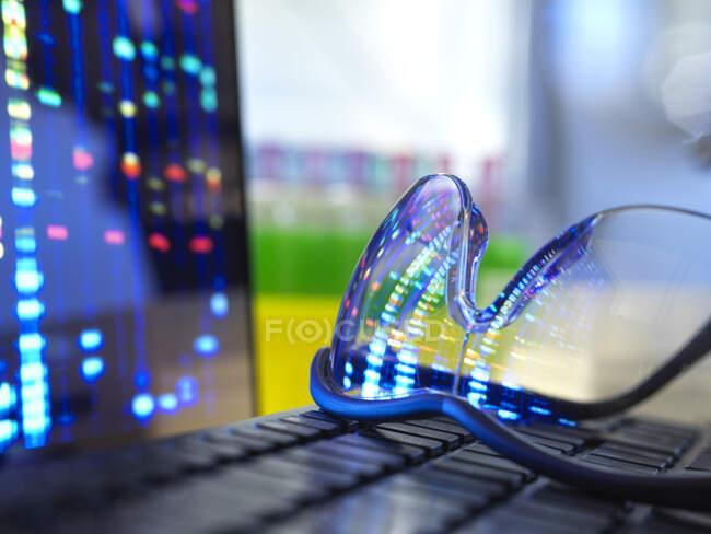 Результаты анализа ДНК в защитных очках, лежащих на клавиатуре ноутбука — стоковое фото