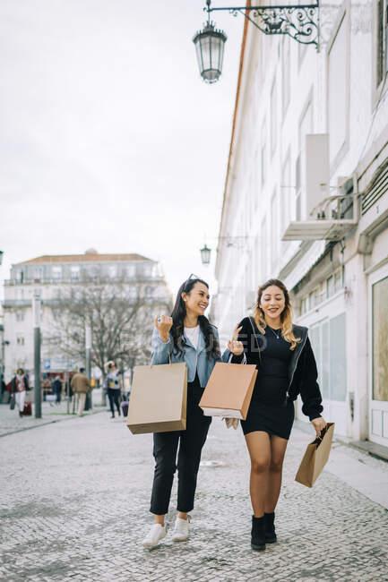 Deux jeunes femmes marchant dans la rue avec des sacs à provisions, Lisbonne, Portugal — Photo de stock