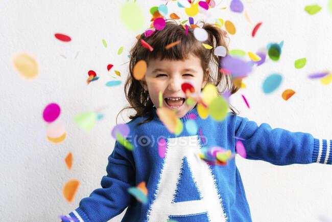 Счастливая маленькая девочка отсасывает конфетти на вечеринке перед белой стеной — стоковое фото