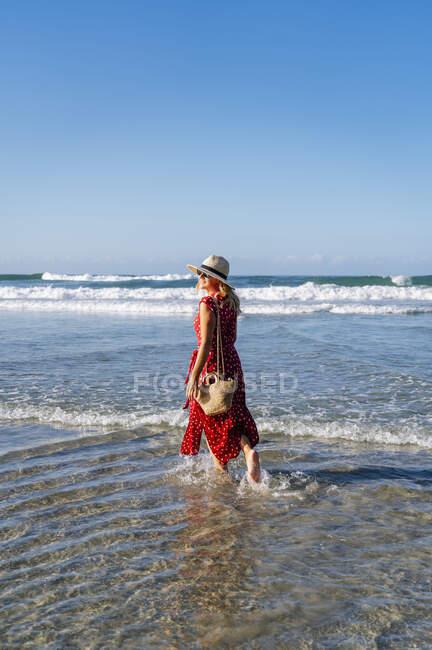 Donna bionda vestita in rosso con cappello e passeggiando sulla spiaggia, Playa de Las Catedrales, Spagna — Foto stock