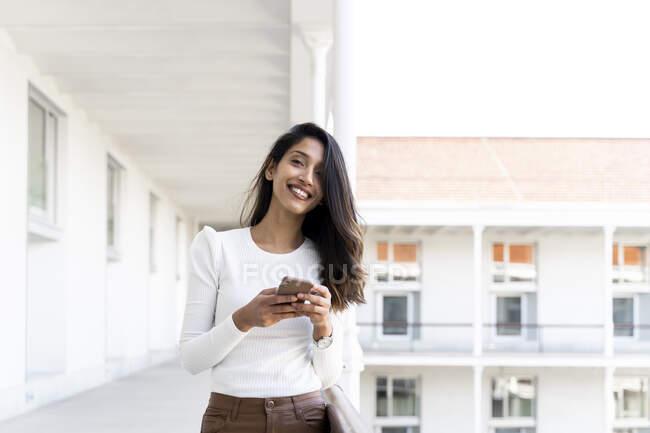 Mujer joven sonriente sosteniendo teléfono inteligente en el balcón - foto de stock