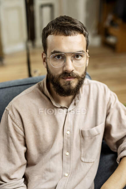 Portrait of young man sitting on his couch, looking at camera — Stock Photo