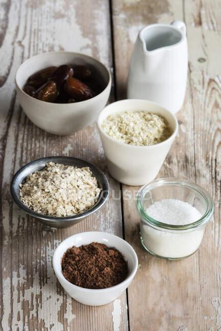 Ingredientes para la elaboración de bolas de proteína (aceite de coco, dátiles, copos de mijo, copos de avena, coco rallado y cacao en polvo) - foto de stock