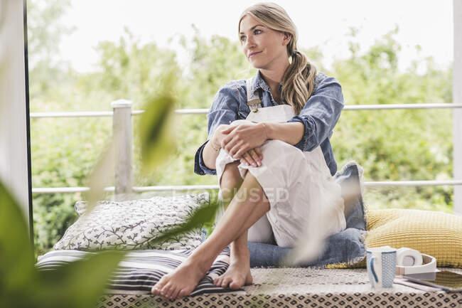 Розслаблена жінка сидить біля вікна вдома. — стокове фото