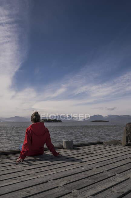 Молода жінка сидить на пристані і дивиться на море (Південно - Східна Ісландія). — стокове фото