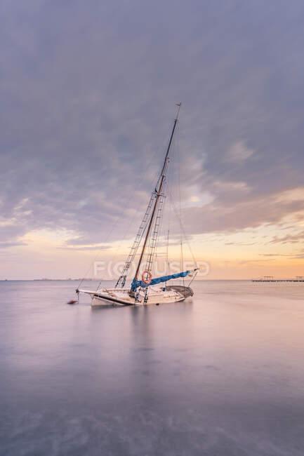 Spagna, Murcia, Santiago de la Ribera, Barca a vela abbandonata sul mare calmo al tramonto — Foto stock
